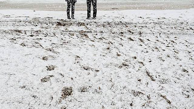 Paar am Strand bei Barcelona im Schneegestöber