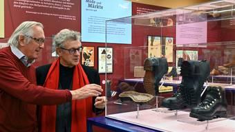Ballyana-Pressechef Martin Matter (links) und Historiker André Schluchter (rechts) im Gespräch bei einer Vitrine.