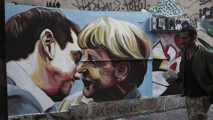 Ein Mann geht in Athen an einem Graffiti vorbei, das den griechischen Premierminister Alexis Tsipras und Angela Merkel, Kanzlerin von Griechenland-Gläubiger Deutschland, zeigt.