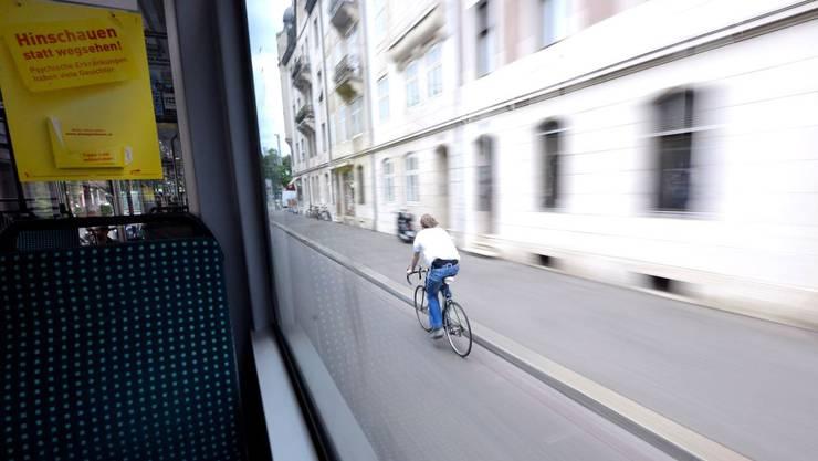 Wie so viele ohne Helm unterwegs: Ein Velofahrer überholt das 2er-Tram kurz vor dem Wettsteinplatz.