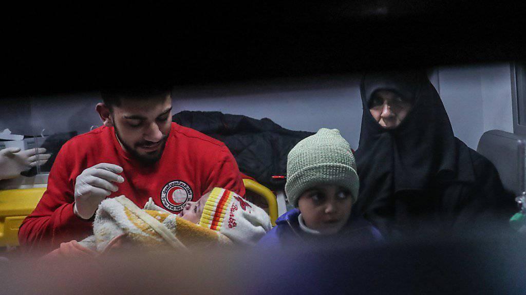Rothalbmond-Helfer beim Abtransport eines kranken Kindes mit Angehörigen aus Ost-Ghuta