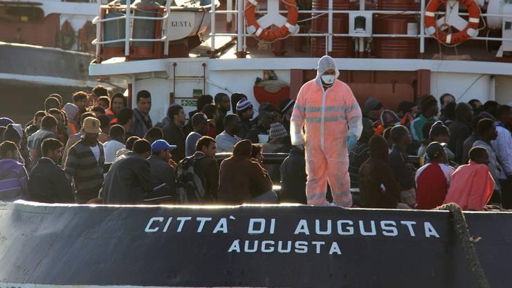 Vor dem Schritt ins gelobte Land: Diese Männer sind im Morgengrauen von einem Schiff der Marine gerettet worden. Nun warten sie im Hafen von Pozzallo darauf, in eines der Erstaufnahmezentren gebracht zu werden. Der Staat ist mit einem Grossaufgebot da. Die Beamten schützen sich vor Ebola.