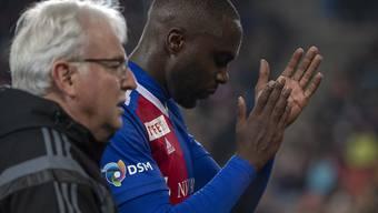 Basels Eder Balanta verlässt den Platz verletzt, begleitet vom Mannschaftsarzt Felix Marti.
