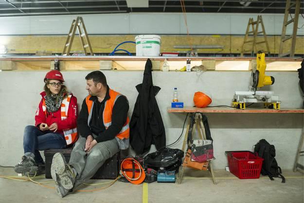 Eine Unia-Mitarbeiterin spricht mit einem Bauarbeiter am Streik auf der SBB Baustelle am Hauptbahnhof in Zürich