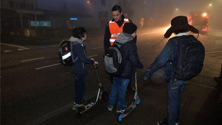 Stefan Zybach erklärt den Trottinett-Fahrern, dass auch sie Licht haben müssen.