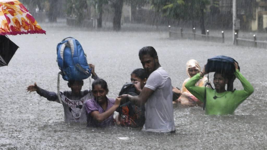 Menschen auf einer überfluteten Strasse in der indischen Metropole Mumbai. (Archivbild)