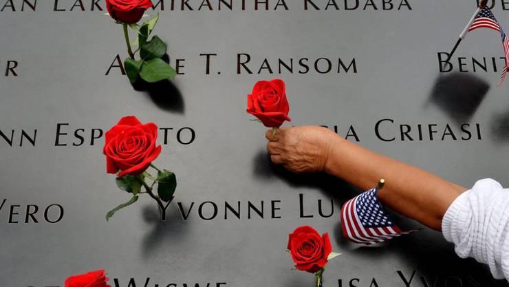 Im Gedenken an die Terroranschläge auf das World Trade Center vom 11. September 2001 in New York zieren Rosen die Gedenktafeln für die Verstorbenen.