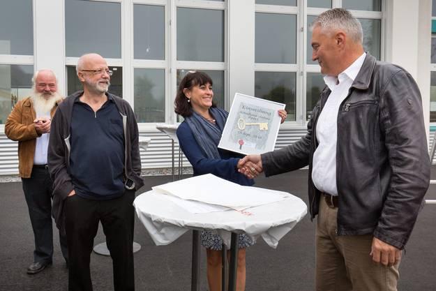 Schlüsselübergabe von Gemeindepräsident Albert Studer (rechts) an Schulleiterin Patricia Segura und Schulleiter Max Wyss (links).