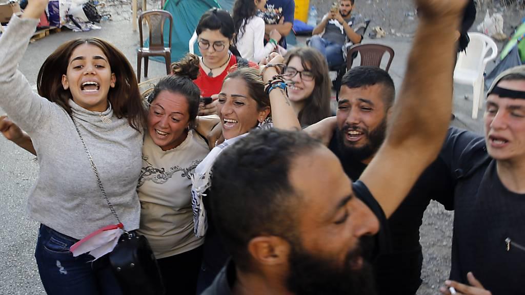Libanesische Anti-Regierungsprotestler feiern in der Hauptstadt Beirut den Rücktritt von Ministerpräsident Saad Hariri.
