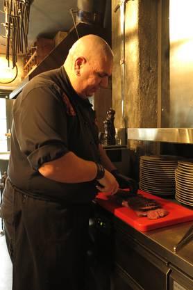 """Chefkoch Samy Scheller alias """"Big Sam"""" bereitet auf dem Buchenholzgrill das Roast Beef für seine Gäste zu."""