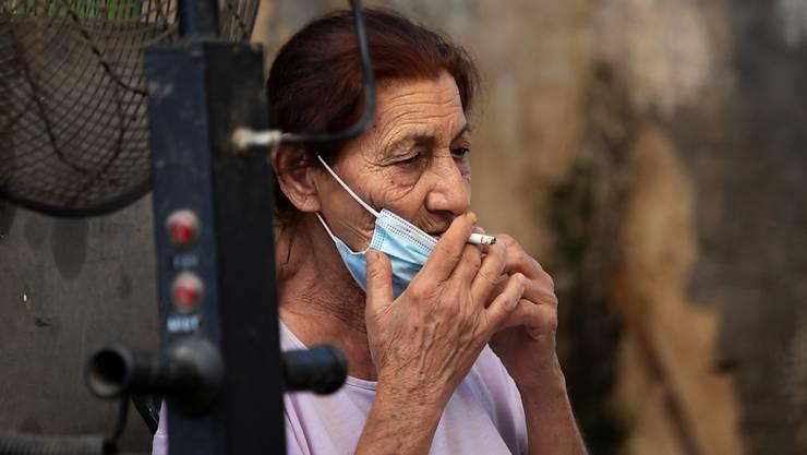 Eine Frau nimmt ihre Gesichtsmaske ab und raucht eine Zigarette auf einem Lebensmittelmarkt. Zu Beginn der weltweiten Corona-Pandemie galt Israel vielen als leuchtendes Beispiel für eine rasche und erfolgreiche Eindämmung. Doch inzwischen steht das Mittelmeerland schlechter da als die meisten europäischen Länder, ein zweiter Lockdown erscheint unausweichlich. Foto: Oded Balilty/AP/dpa