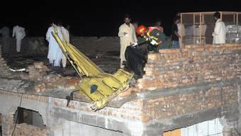 Retttungskräfte untersuchen Trümmerteile des abgestürzten Flugzeugs der Bhoja Air in Pakistan