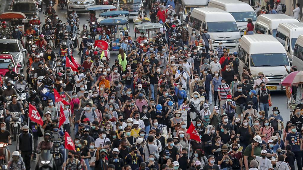 Demonstranten gehen während eines regierungskritisches Protestes über eine Straße in Bangkok in Richtung des Strafgerichts. Foto: Sakchai Lalit/AP/dpa