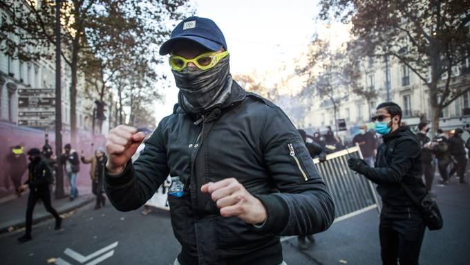 Kampfbereit: Ein Demonstrant bedroht in Paris einen Journalisten. Tausende waren am Wochenende auf der Strasse, um gegen das umstrittene Polizeigesetz zu demonstrieren.