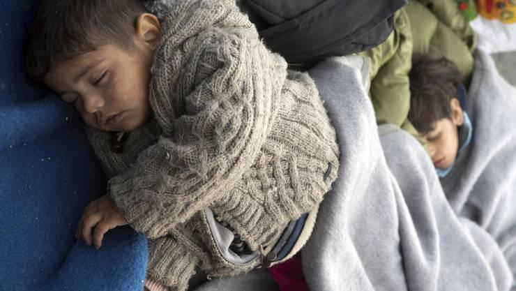 Ein Flüchtlingskind schläft mit warmen Decken.