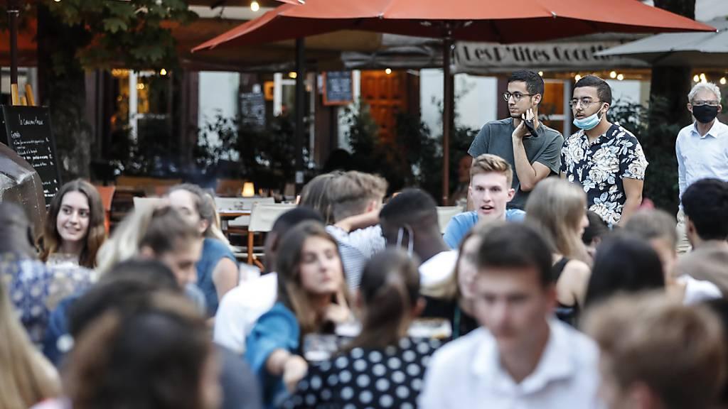 Jugendliche sitzen an Tischen auf der Terrasse eines Cafés. Angesichts steigender Corona-Zahlen hat Frankreichs Premierminister Castex an das Verantwortungsbewusstsein seiner Landsleute appelliert und warnte vor der wachsenden Ausbreitung des Virus im Land. Foto: Jean-Francois Badias/AP/dpa