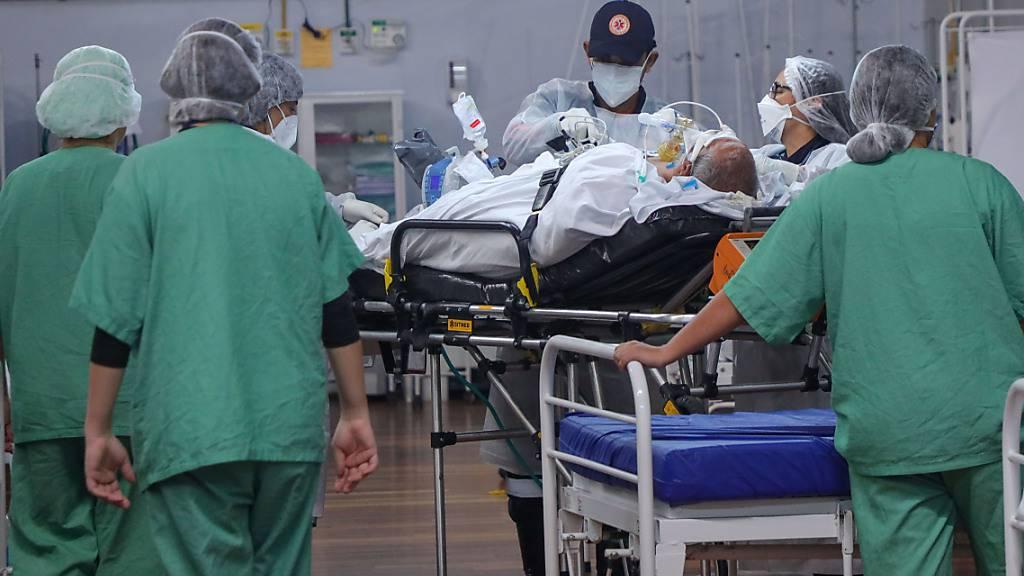dpatopbilder - Mitarbeiter versorgen in einem Feldlazarett in Santo Andre einen Corona-Patienten. Foto: Vanessa Carvalho/ZUMA Wire/dpa