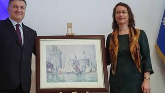 """Die Ukraine hat ein gestohlenes Bild des Künstlers Paul Signac im Wert von etwa 1,5 Millionen Euro an Frankreich zurückgegeben. """"Das ist Balsam auf die Wunde nach dem Feuer von Notre-Dame"""", sagte Frankreichs Botschafterin Isabelle Dumont (rechts) bei der Übergabe."""