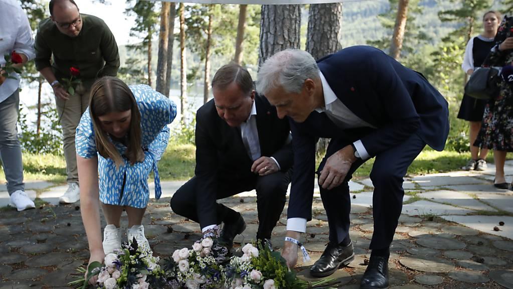 Astrid Hoem, Vorsitzende der AUF, Stefan Löfven, Ministerpräsident von Schweden, und Jonas Gahr Støre, Vorsitzender der norwegischen Arbeiterpartei, legen Blumen nieder.