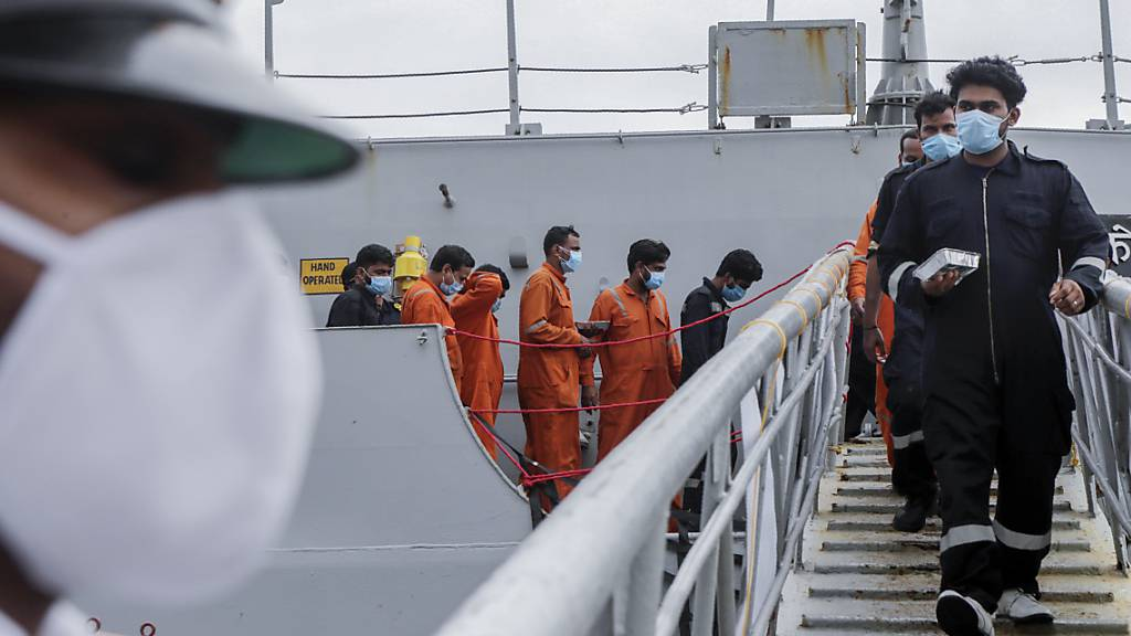 Gerettete Besatzungsmitglieder eines gesunkenen Lastkahns gehen von Bord des indischen Marineschiffs INS Kochi. Der für Bohrungen eingesetzte Lastkahn sank im Arabischen Meer, nachdem der Zyklon «Tauktae» auf die Westküste traf. Foto: Rajanish Kakade/AP/dpa