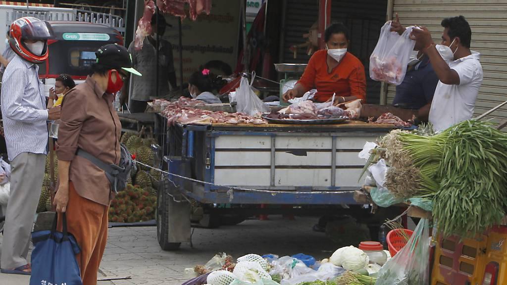 Lokale Verkäufer verkaufen ihr Gemüse, Fisch und Fleisch an einem Marktstand, nachdem ein coronabedingter Lockdown aufgehoben wurde. Foto: Heng Sinith/AP/dpa