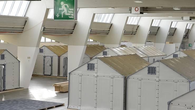 In einer Messehalle in Zürich-Oerlikon werden ab Januar vorübergehend 250 Asylsuchende in Selbstbau-Häuschen der Ikea Stiftung untergebracht.