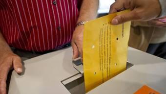 Eine Frau wirft ihren Abstimmungszettel in die Urne (Symbolbild)