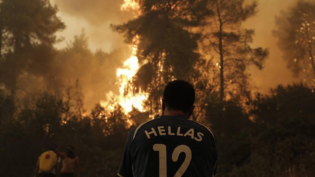 Einwohner und freiwillige Helfer kämpfen gegen einen Waldbrand in der Nähe von Pefki auf der Insel Euböa. Klimaextreme wie Hitzewellen und Starkregen seien jetzt in jeder Region der Welt zu beobachten, stellt der jüngste IPCC-Bericht fest.