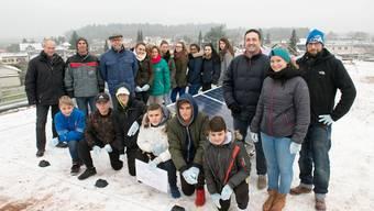Schülerinnen und Schüler sowie Lehrkräfte und Behördenmitglieder auf dem Dach mit der Solaranlage.