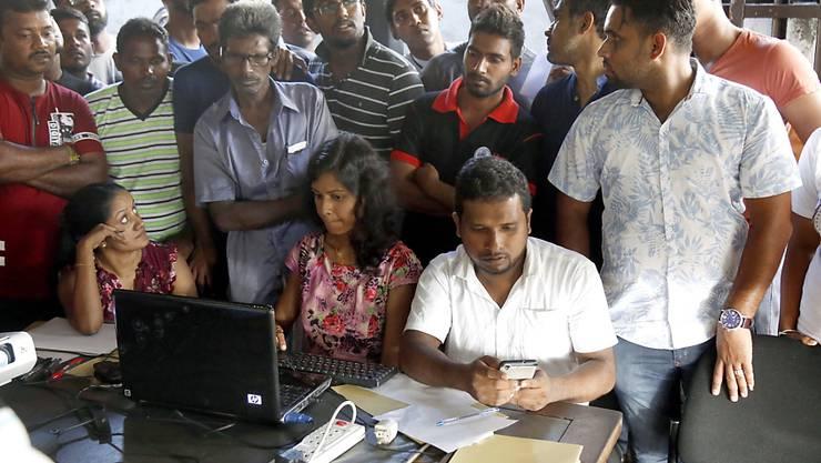 Menschen in Sri Lanka versuchen nach den Anschlägen, am Bildschirm eines Laptops vermisste Angehörige zu identifizieren.