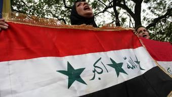 Eine Irakerin zeigt Flagge (Symbolbild)