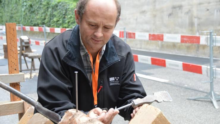 Daniel Huber schlägt Nägel in den Stamm, um mit einem Faden zu testen, ob der Bohrer gerade ansetzt.