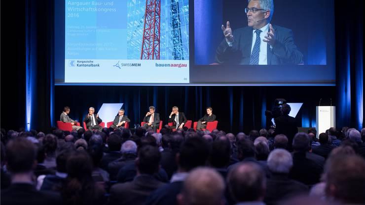 Das Podium am Bau- und Wirtschaftskongress, gross im Bild: Thomas Buchmann, Leiter des Amts für Wirtschaft und Arbeit.
