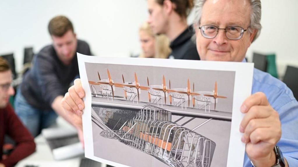 Der Ingenieur und Informatiker Peter Kielhorn hält eine Seitenansicht des Flugbootes DO X, während die Studenten Dominik Bodenmüller, Kai Pete, Sofia Stich und Pascal Mannig im Hintergrund an der Konstruktion des legendären Fluggeräts tüfteln.