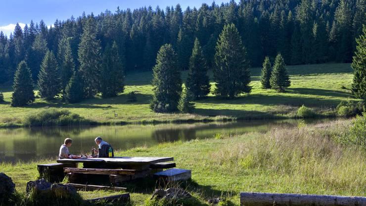 Wanderer machen eine Pause an einem kleinen See in der Nähe des Weilers Le Peu-Pequinot bei Le Noirmont im Kanton Jura.