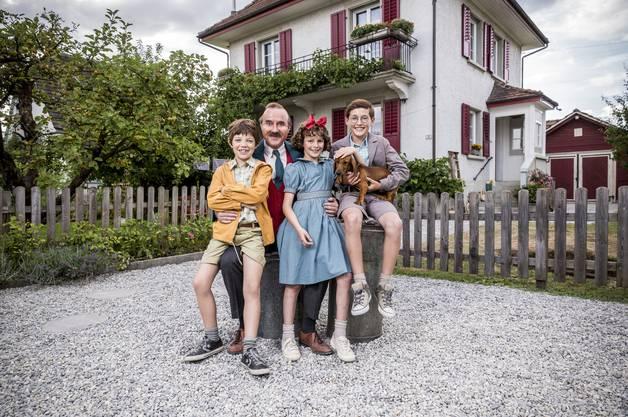 Papa Moll mit seinen Kindern vor dem Haus, in dem die Familie (mit Mama Moll und Hund Tschips) wohnen.