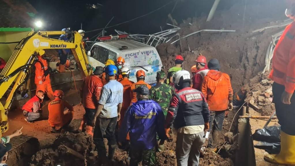 Retter suchen am Ort eines Erdrutsches im Dorf Cihanjuang nach Menschen. Foto: -/Indonesian National Disaster Mitigation Agency/AP/dpa