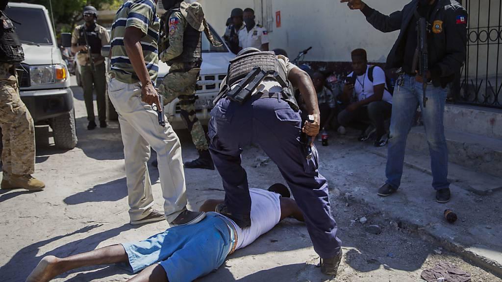 Polizisten halten einen Insassen nach einem Ausbruchsversuch aus einem Gefängnis fest. Foto: Dieu Nalio Chery/AP/dpa