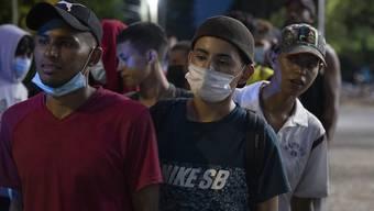Migranten aus Honduras stehen nebeneinander und warten auf Hilfe auf ihrem Weg in Richtung USA. Foto: Moises Castillo/AP/dpa