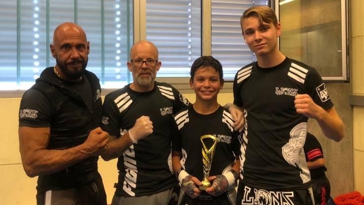 Nevio Trimarco (zweiter von rechts) präsentiert die Trophäe vom Wochenende. Beim Training zählt er auf die Unterstützung seiner Trainer Marco Witzig (zweiter von links) und Patrick Berglas (links).