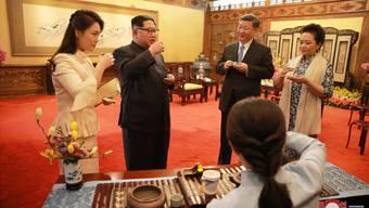 Nordkoreas Machthaber Kim Jong Un (Mitte links) mit Ehefrau Ri Sol Ju (links) im Gespräch mit Chinas Präsident Xi Jinping und dessen Ehefrau Peng Liyuan.