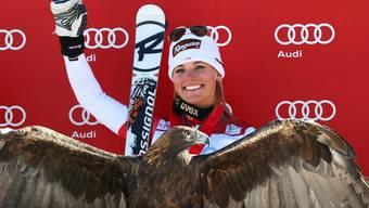 Lara Gut winkt, vor ihr sitzt ein Adler.