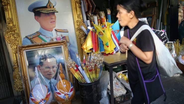 Ein Frau läuft in der thailändischen Hauptstadt Bangkok an den Porträts des verstorbenen Königs Bhumibol Adulyadej (unten) und des Kronprinzen Maha Vajiralongkorn (oben) vorbei. Letzterer will die Nachfolge seines Vaters frühestens in einem Jahr antreten.