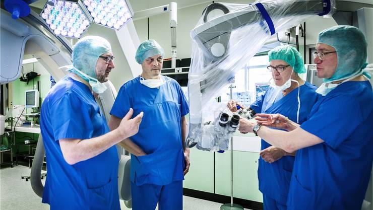Patient Sascha Stoppa (2. v. l.) kehrt gesund in den hybriden Operationssaal zurück. Der OP ist ein Prototyp, es dauerte drei Jahre, bis er optimal eingerichtet war. Javier Fandino, Chefarzt Neurochirurgie (ganz rechts), und Marco Necchi, Leiter OP-Saal, zeigen das Operationsmikroskop. Ganz links vor dem Angiografiegerät steht der Chef der Neuroradiologie, Luca Remonda. Chris Iseli