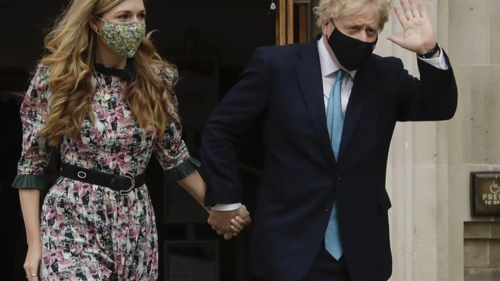 dpatopbilder - Boris Johnson (r), Premierminister von Großbritannien, winkt, als er mit seiner Verlobten Carrie Symonds nach ihrer Stimmenabgabe das Methodist Central Hall verlässt. Foto: Matt Dunham/AP/dpa