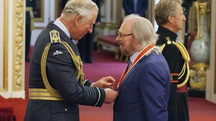 Barry Gibb von den Bee Gees (r) plaudert mit Prinz Charles, nachdem ihn dieser zum Ritter geschlagen hat.