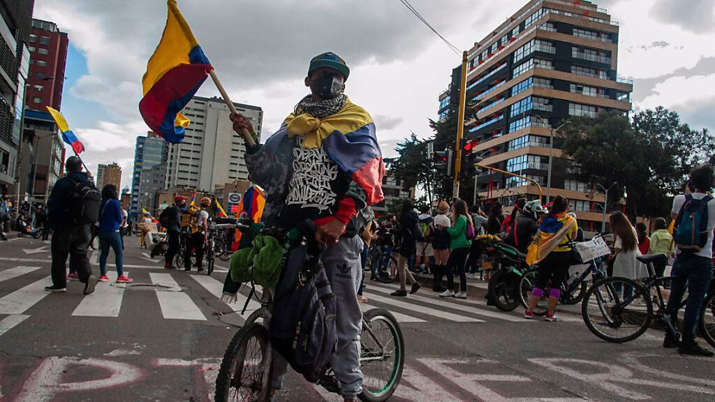 Ein Demonstrant in Bogotá schwenkt eine kolumbianische Flagge bei einer Protestaktion gegen die Gewaltanwendung durch die Polizei. Der kolumbianische Präsident Iván Duque hat nach tagelangen Protesten den Einsatzbefehl für die Sicherheitskräfte verschärft. Foto: Chepa Beltran/LongVisual via ZUMA Wire/dpa