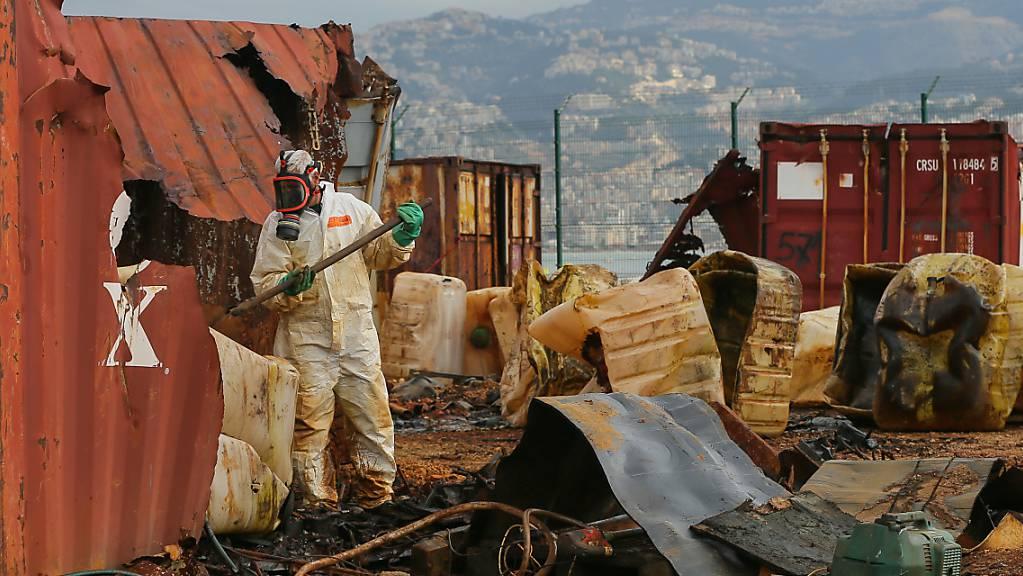 Ein Arbeiter entfernt im zerstörten Hafen von Beirut Behälter mit Salzsäure aus verrotteten Containern. Foto: Marwan Naamani/dpa