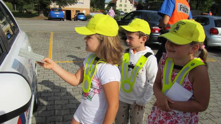 Paula (links), Tizian und Samanta (rechts) kontrollieren Führerausweise und Fahrzeugpapiere.