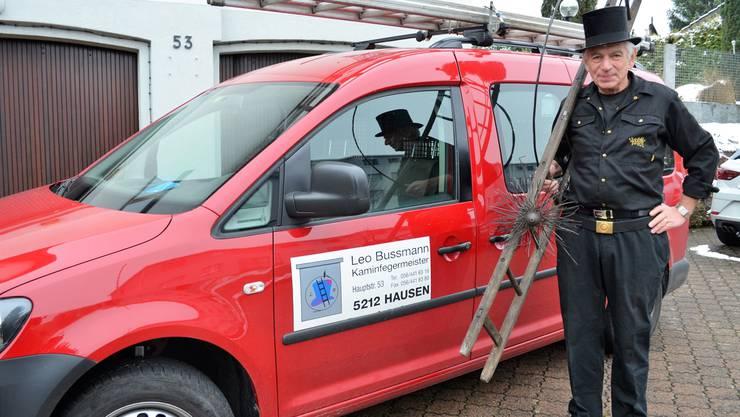 Kaminfegermeister Leo Bussmann posiert in Arbeitskleidung, mit Leiter und Werkzeug vor seinem Haus.